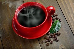 Cup of fresh coffee. With coffee beans on wooden table Royalty Free Stock Photo