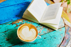 Fresh coffee and book on a wooden table Stock Image