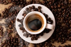 A cup of fresh coffee on burlap. A scattering of coffee beans with a cup of coffee. Coarse fabric. For banner stock image