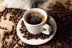 A cup of fresh coffee on burlap. A scattering of coffee beans with a cup of coffee. Coarse fabric. For banner stock photography