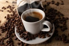A cup of fresh coffee on burlap. A scattering of coffee beans with a cup of coffee. Coarse fabric. For banner royalty free stock image
