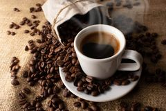 A cup of fresh coffee on burlap. A scattering of coffee beans with a cup of coffee. Coarse fabric. For banner stock images