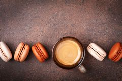 Cup of fresh coffee and cake macaron or macaroon on brown table top view stock images