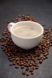 Cup of fresh coffee with coffee beans on black background Royalty Free Stock Photos