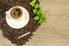 Cup of fresh coffee, coffee beans, cigar and mint tea flowers on table. Close Stock Images