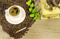 Cup of fresh coffee, coffee beans, coffee grinder, cigar and mint flowers. Close stock images