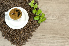 Cup of fresh coffee, coffee beans, and mint tea flowers on wooden table. Close Royalty Free Stock Images