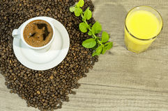 Cup of fresh coffee, coffee beans,  orang juice and mint tea leaves Stock Photo