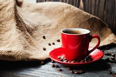 Cup of fresh coffee with coffee beans on wooden table Stock Image