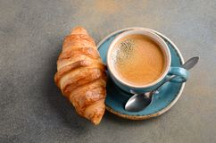 Cup of fresh coffee with croissant on concrete background. stock photography