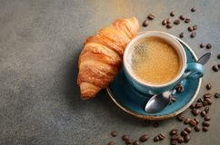 Cup of fresh coffee with croissant on concrete background. stock images