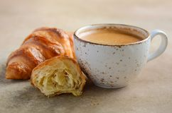 Cup of fresh coffee with croissant on concrete background royalty free stock photography