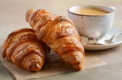 Cup of fresh coffee with croissant on concrete background stock images