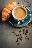 Cup of fresh coffee with croissant on concrete background. royalty free stock image