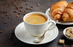 Cup of fresh coffee with croissants on dark background. Selective focus royalty free stock photography