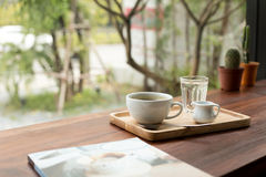 A cup of fresh coffee with glass of water and book. On wooden table stock photography