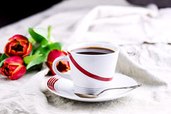Cup of fresh coffee onl linen napkins Tulips next to cup Royalty Free Stock Images