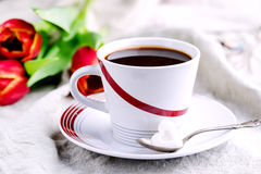 Cup of fresh coffee onl linen napkins Tulips next to cup Stock Image