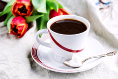 Cup of fresh coffee onl linen napkins Tulips next to cup Royalty Free Stock Photo