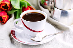 Cup of fresh coffee onl linen napkins Tulips next to cup Royalty Free Stock Photos