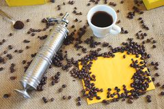 Cup of fresh coffee. Coffee cup and vintage coffee grinder with coffee beans on burlap Stock Images