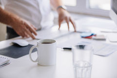 Cup of fresh coffee on work desk. Close up shot of cup of fresh coffee on desk with man working in background royalty free stock image