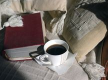 Book And Morning Coffee. Cup of fresh cooffee and old book laid on the sofa Royalty Free Stock Image