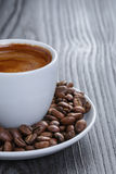 Cup of fresh espresso with beans. On black wood table royalty free stock images