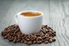 Cup of fresh espresso with coffee beans on oak Stock Images