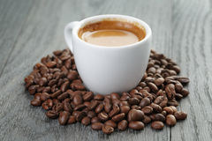 Cup of fresh espresso with coffee beans on oak Stock Photo