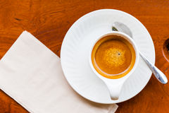 Cup of fresh espresso with spoon, napkin on table. View from above royalty free stock images