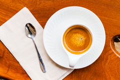 Cup of fresh espresso with spoon, napkin on table. Cup of fresh espresso with spoon, napkin on wood table, view from above stock photos