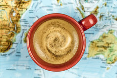 Cup of fresh frothy coffee on a world map. Colorful red cup of fresh frothy coffee on a world map in a conceptual image viewed from above Royalty Free Stock Images