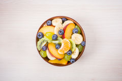 Cup of fresh fruit salad on a wooden background Stock Photos