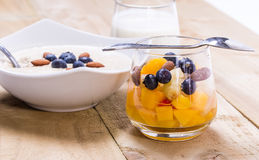 Cup of fresh fruits. Fresh fruity dessert with bowl of porridge on the wooden background Royalty Free Stock Images