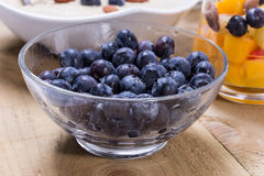 Cup of fresh fruits. Cup of fruity dessert with fresh peach, blueberries on the wooden table Stock Photography