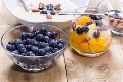Cup of fresh fruits. Cup of fruity dessert with fresh peach, blueberries on the wooden table Royalty Free Stock Photo