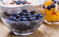 Cup of fresh fruits. Cup of fruity dessert with fresh peach, blueberries on the wooden table Royalty Free Stock Photography