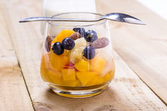 Cup of fresh fruits. Cup of fruity dessert with fresh peach, blueberries on the wooden table Royalty Free Stock Image