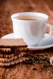Cup of fresh herbal tea and some cookies. Closeup on wooden table Stock Photos
