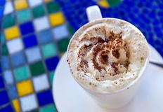Cup of fresh hot cappuccino stands on a table in the style of Greek mosaic. Top view Stock Photo