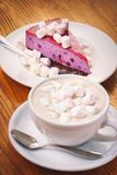 Cup of fresh hot chocolate drink with marshmallow and a piece of blueberry cake on the wooden table royalty free stock images