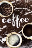 The word coffee is written on ground coffee. A cup of fresh hot coffee with foam, a cup of ground and a cup of coffee beans next to the word `coffee` written on Stock Image
