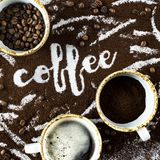 The word coffee is written on ground coffee. A cup of fresh hot coffee with foam, a cup of ground and a cup of coffee beans next to the word `coffee` written on Stock Photography