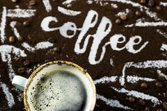 The word coffee is written on ground coffee. A cup of fresh hot coffee with foam next to the word `coffee` written on the ground coffee Royalty Free Stock Photos