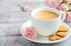Cup of fresh morning coffee with pink carnation flowers on a wooden background. Valentine`s day concept. royalty free stock photo