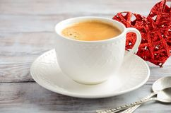 Cup of fresh morning coffee on a wooden background. Valentine`s day concept. stock photos