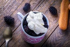 Cup of fresh natural blackberries with whipped cream. And biscuits. Spoon and wooden table Stock Image