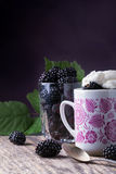 Cup of fresh natural blackberries with whipped cream. And biscuits. Spoon and wooden table Stock Photography