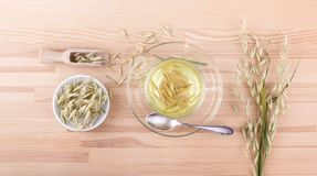 Cup of fresh oat tea. Top view of a cup of fresh oat tea on a wooden background Royalty Free Stock Photo